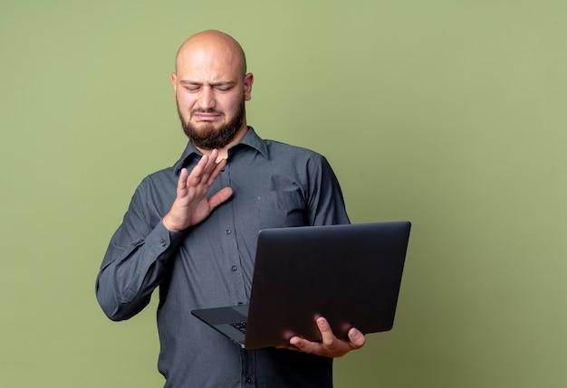 Ontevreden jonge kale call center man houden en kijken naar laptop en doen geen gebaar geïsoleerd op olijfgroene achtergrond met kopie ruimte