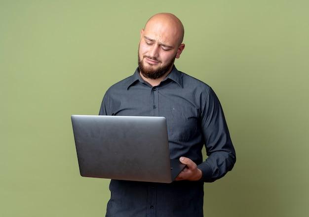 Ontevreden jonge kale call center man houden en kijken naar laptop geïsoleerd op olijfgroene achtergrond met kopie ruimte