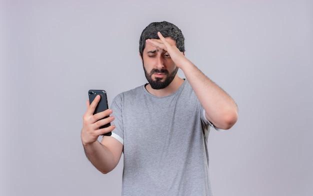Ontevreden jonge knappe blanke man houden en kijken naar mobiele telefoon met hand op voorhoofd geïsoleerd op een witte achtergrond met kopie ruimte