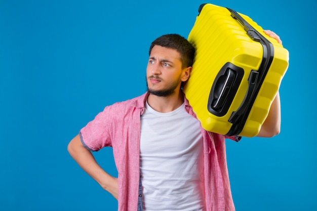 Ontevreden jonge knappe de holdingskoffer die van de reizigerskerel opzij met fronsend gezicht kijken die zich over blauwe achtergrond bevinden