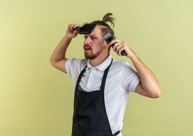 Ontevreden jonge knappe kapper met kam en tondeuse in de buurt van hoofd geïsoleerd op olijfgroene achtergrond met kopie ruimte