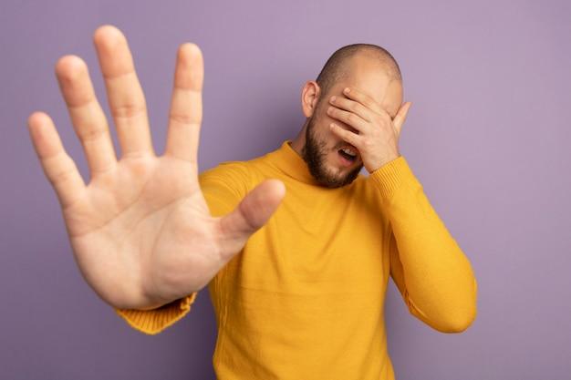 Ontevreden jonge knappe kerel bedekt gezicht met hand die hand opheft die op paars wordt geïsoleerd