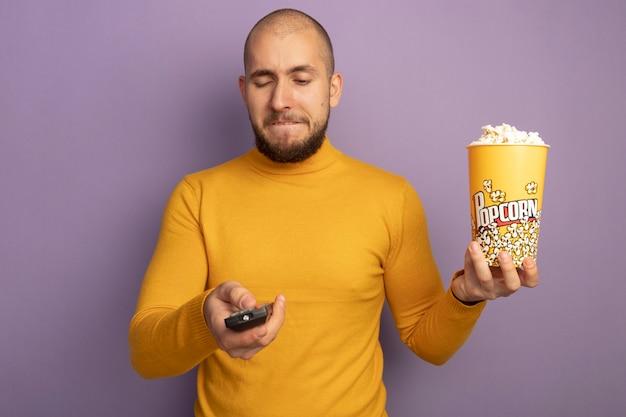 Ontevreden jonge knappe kerel die emmer popcorn met afstandsbediening van de tv houdt die op purpere muur wordt geïsoleerd