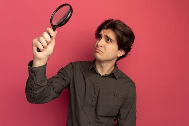 Ontevreden jonge knappe kerel met een zwart t-shirt die opheft en kijkt naar vergrootglas geïsoleerd op roze muur