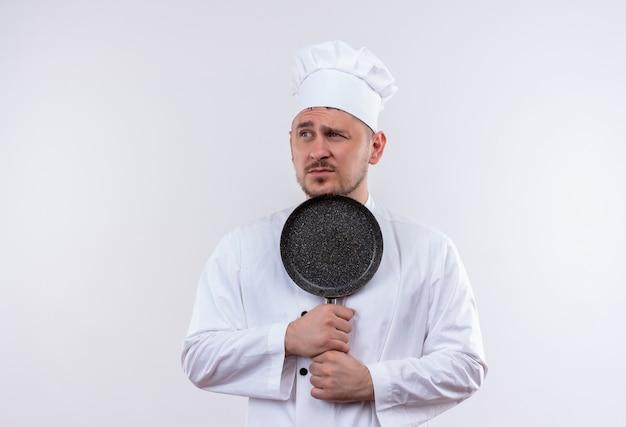 Ontevreden jonge knappe kok in de pan die van de chef-kok de eenvormige holding kant bekijkt die op witte ruimte wordt geïsoleerd