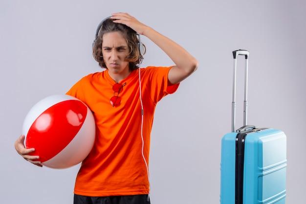 Ontevreden jonge knappe man in oranje t-shirt met koptelefoon met opblaasbare bal aanraken hoofd op zoek naar een camera met fronsend gezicht in de buurt van koffer