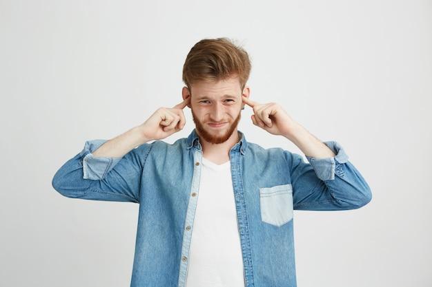 Ontevreden jonge knappe man met baard fronsen sluitende oren.