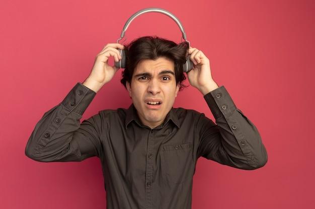 Ontevreden jonge knappe man met een zwart t-shirt die een koptelefoon op zijn hoofd zet, geïsoleerd op een roze muur