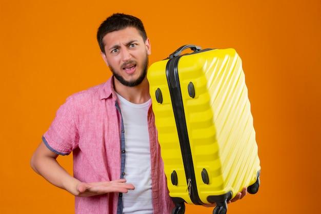 Ontevreden jonge knappe reiziger man met koffer kijken camera geërgerd wijzend met arm van hand naar zijn koffer staande op oranje achtergrond