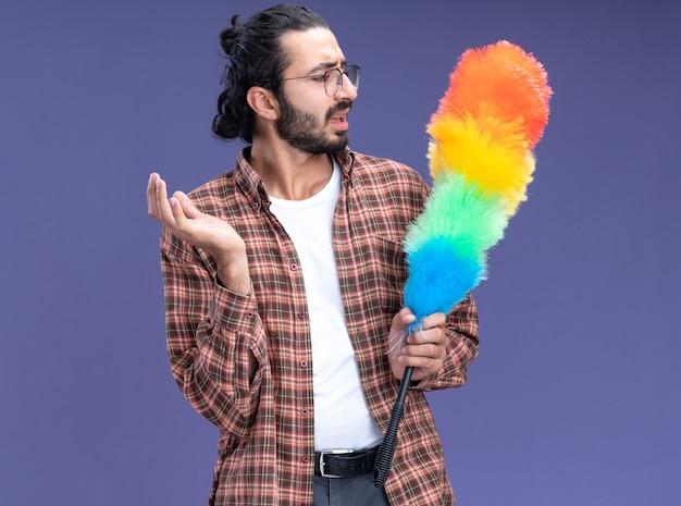 Ontevreden jonge knappe schoonmaakster die een t-shirt draagt en naar een plumeau kijkt die op een blauwe muur is geïsoleerd