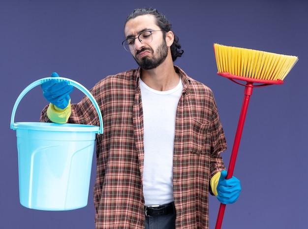 Ontevreden jonge knappe schoonmaakster die t-shirt en handschoenen draagt die emmer met zwabber houden die op blauwe muur wordt geïsoleerd