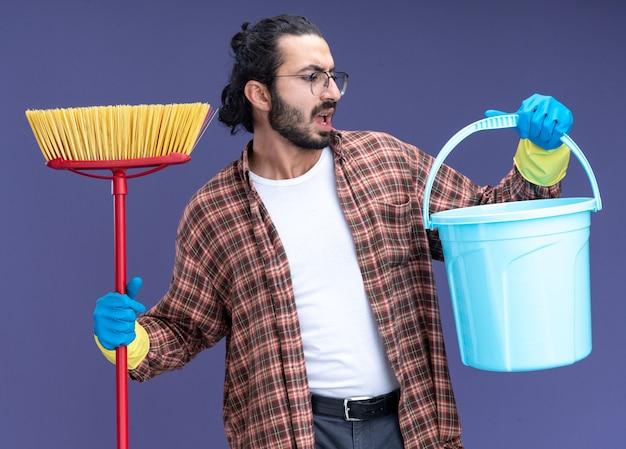 Ontevreden jonge knappe schoonmaakster die t-shirt en handschoenen draagt die zwabber houden die emmer in zijn hand bekijkt die op blauwe muur wordt geïsoleerd