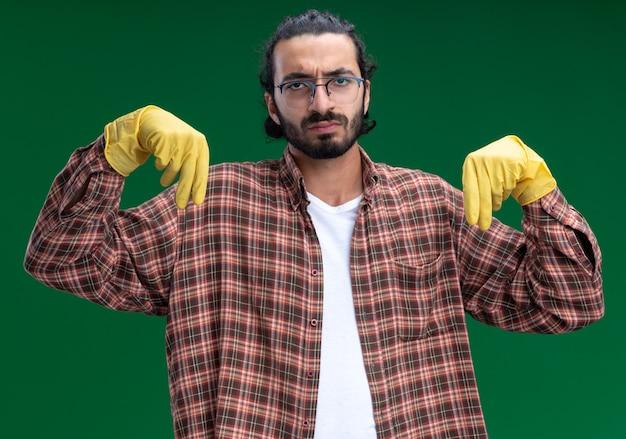Ontevreden jonge knappe schoonmaakster met een t-shirt en handschoenen die doet alsof hij iets vasthoudt dat op een groene muur is geïsoleerd
