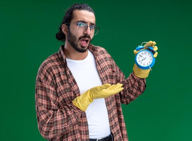 Ontevreden jonge knappe schoonmaakster met een t-shirt en handschoenen die vasthoudt en wijst op een wekker geïsoleerd op een groene muur