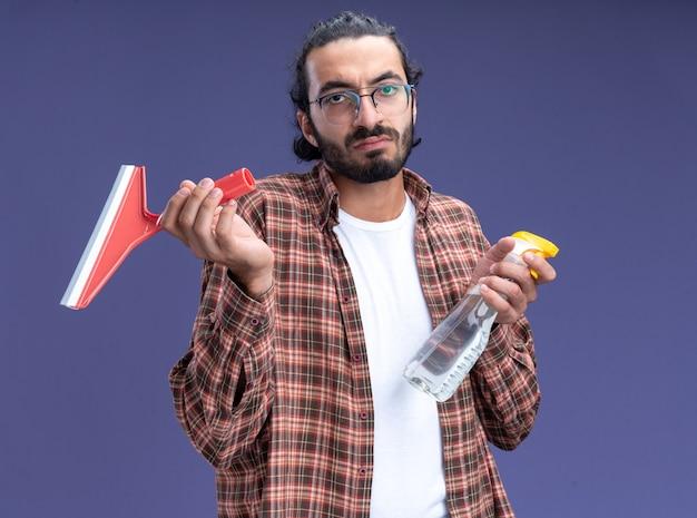 Ontevreden jonge knappe schoonmaakster met een t-shirt met een dweilkop met een spuitfles geïsoleerd op een blauwe muur