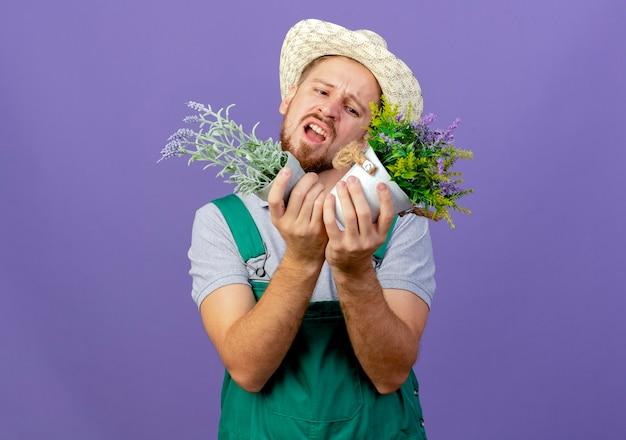 Ontevreden jonge knappe slavische tuinman in uniform en hoed houden en kijken naar bloempotten geïsoleerd op paarse muur met kopie ruimte