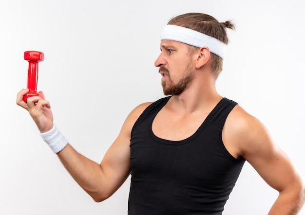 Ontevreden jonge knappe sportieve man die hoofdband en polsbandjes draagt die halter houden en het bekijken geïsoleerd op witte ruimte