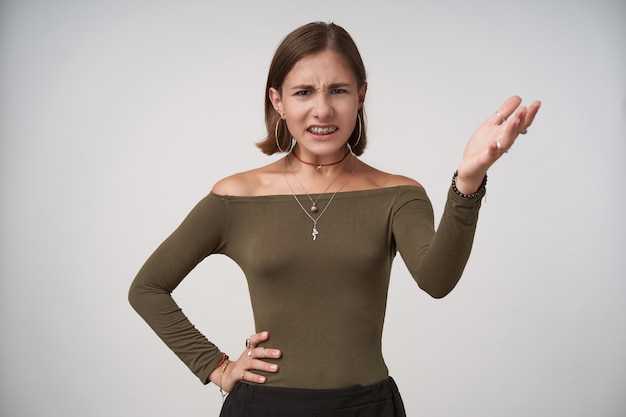 Ontevreden jonge kortharige brunette vrouw met casual kapsel houdt haar hand omhoog terwijl ze ontevreden naar voren kijkt, geïsoleerd over witte muur