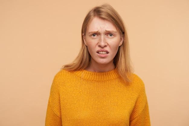 Ontevreden jonge langharige roodharige vrouw fronste ontevreden haar gezicht, gekleed in vrijetijdskleding terwijl ze poseerde op beige