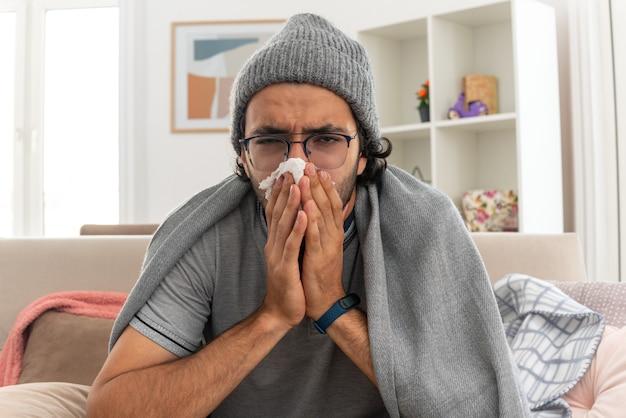 Ontevreden jonge man met optische bril gewikkeld in plaid met wintermuts veegt zijn neus af met tissues kijkend naar de voorkant zittend op de bank in de woonkamer
