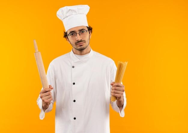 Ontevreden jonge mannelijke kok die eenvormige chef-kok en glazen draagt die spaghetti en deegroller houdt die op gele muur wordt geïsoleerd