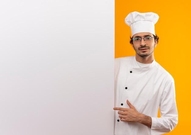 Ontevreden jonge mannelijke kok die eenvormige chef-kok en glazen draagt die witte muur houden die op gele muur met exemplaarruimte wordt geïsoleerd