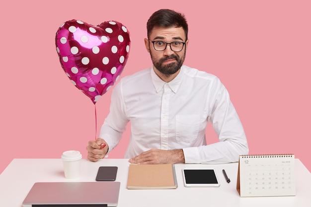 Ontevreden jonge mannelijke romanticus met donkere stoppels, gekleed in formele kleding, draagt valentijn, aarzelt om met vriendin te daten