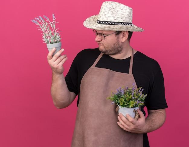 Ontevreden jonge mannelijke tuinman die tuinierende hoed draagt ?? die en bloemen in bloempotten bekijkt die op roze muur worden geïsoleerd