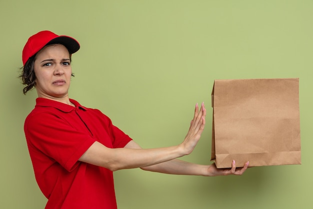 Ontevreden jonge mooie bezorger die een papieren voedselzak vasthoudt en kijkt