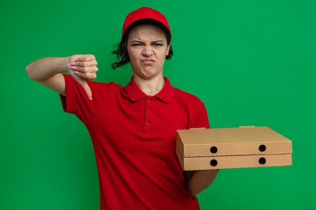 Ontevreden jonge mooie bezorger die pizzadozen vasthoudt en naar beneden wijst