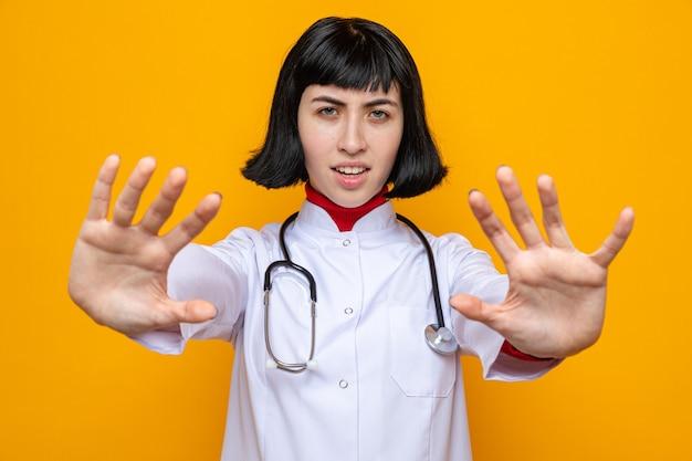 Ontevreden jonge, mooie blanke vrouw in doktersuniform met een stethoscoop die zijn handen uitstrekt