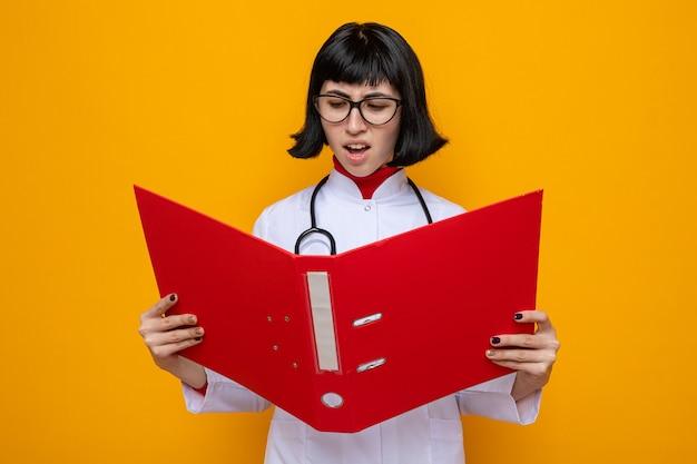 Ontevreden jonge, mooie blanke vrouw met een bril in doktersuniform met een stethoscoop die de bestandsmap vasthoudt en bekijkt