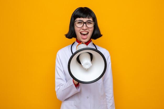 Ontevreden jonge, mooie blanke vrouw met een bril in doktersuniform met een stethoscoop die in de luidspreker schreeuwt