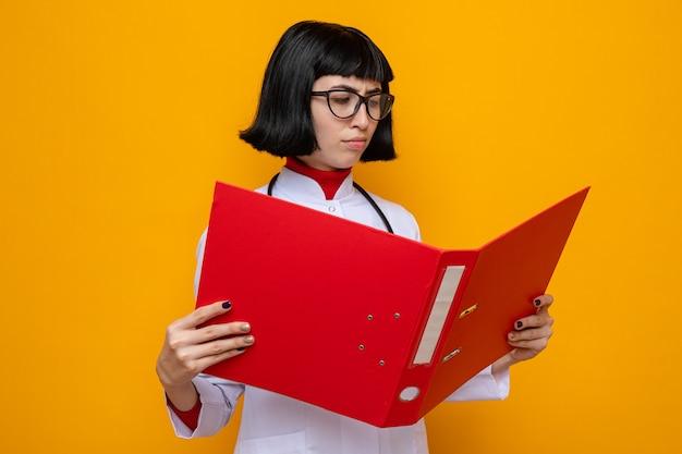 Ontevreden jonge, mooie blanke vrouw met een bril in doktersuniform met een stethoscoop die naar de bestandsmap kijkt