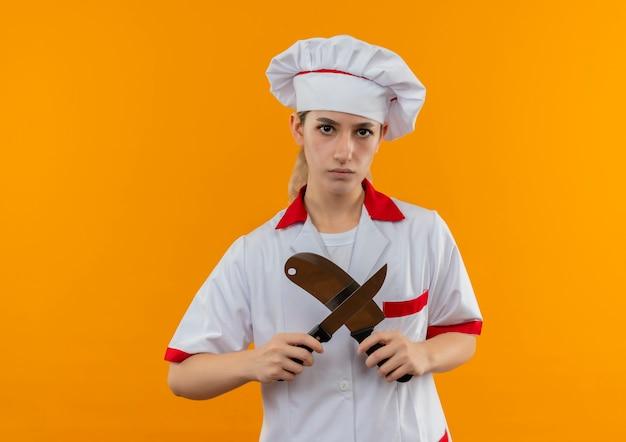 Ontevreden jonge mooie kok in uniform chef-kok gebaren nee met hakmes en mes op zoek geïsoleerd op oranje ruimte