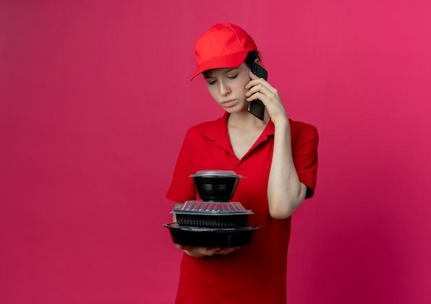 Ontevreden jonge mooie levering meisje dragen rode uniform en pet praten over de telefoon en houden en kijken naar voedsel containers geïsoleerd op karmozijnrode achtergrond met kopie ruimte