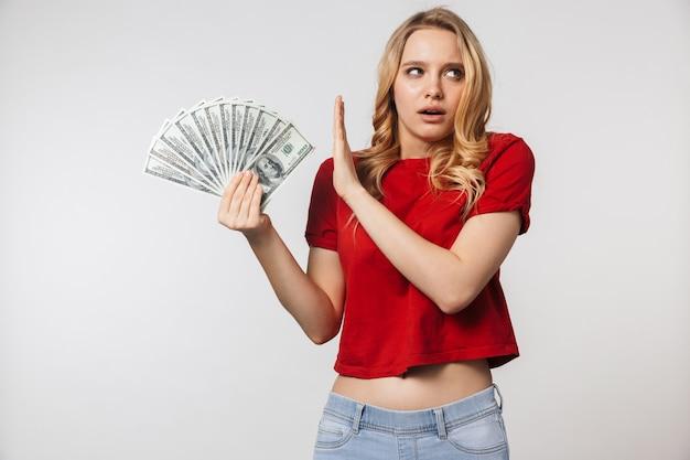 Ontevreden jonge mooie mooie vrouw poseren geïsoleerd over witte muur muur met geld maken stop gebaar Premium Foto