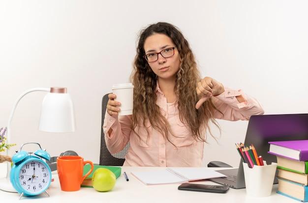 Ontevreden jonge mooie schoolmeisje bril zit aan bureau met school tools haar huiswerk houden koffiekopje en duim omlaag geïsoleerd op witte achtergrond tonen