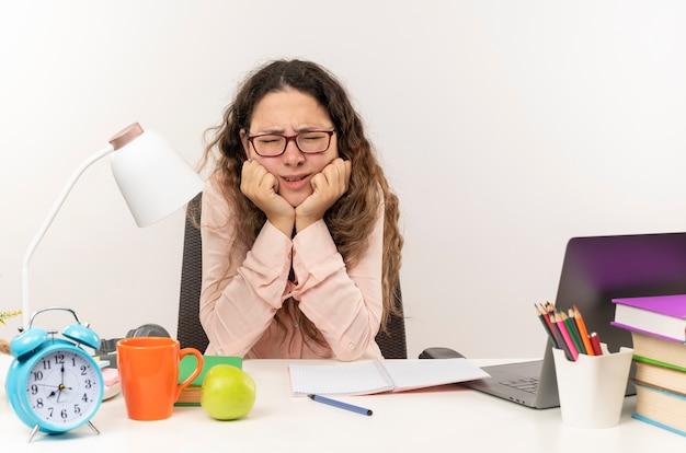 Ontevreden jonge mooie schoolmeisje bril zit aan bureau met school tools haar huiswerk zetten kin met gesloten ogen geïsoleerd op witte achtergrond