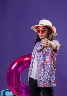 Ontevreden jonge mooie vrouw die de zomerhoed en rode zonnebril draagt die opblaasbare ring houdt