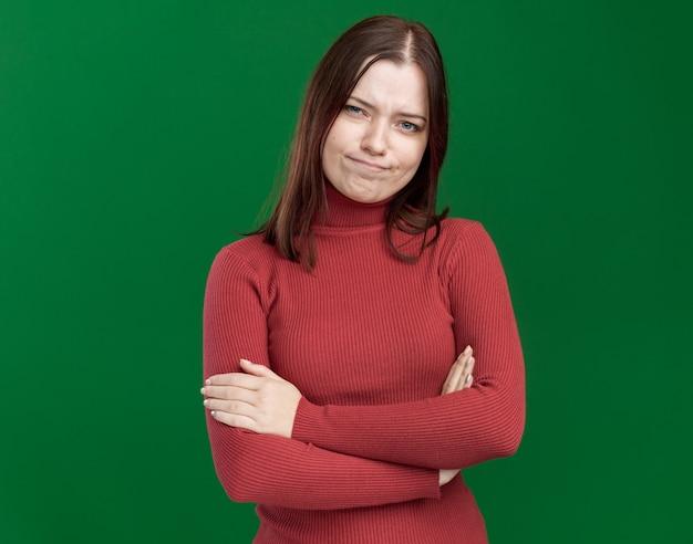 Ontevreden jonge mooie vrouw die met gesloten houding naar de voorkant kijkt geïsoleerd op een groene muur met kopieerruimte