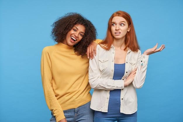 Ontevreden jonge mooie vrouw met foxy haar dat verward handpalm en grijnzend gezicht opheft terwijl ze over de blauwe muur staat met een gelukkige aantrekkelijke gekrulde donkere vriendin