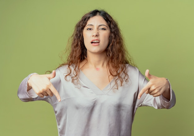 Ontevreden jonge mooie vrouwelijke kantoormedewerker wijst naar beneden geïsoleerd op olijfgroene muur