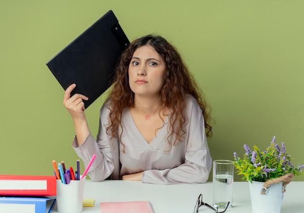 Ontevreden jonge mooie vrouwelijke kantoormedewerker zit aan bureau