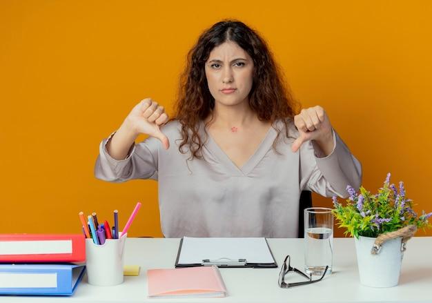 Ontevreden jonge mooie vrouwelijke kantoormedewerker zittend aan een bureau met kantoorhulpmiddelen haar duimen omlaag geïsoleerd op oranje