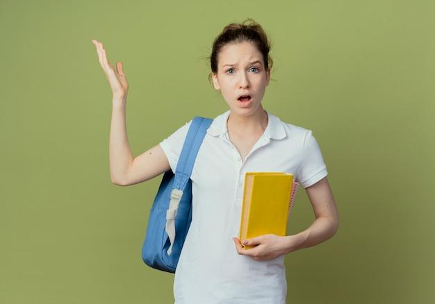 Ontevreden jonge mooie vrouwelijke student die het boek van de achterzakholding draagt en hand opheft die op groene achtergrond met exemplaarruimte wordt geïsoleerd