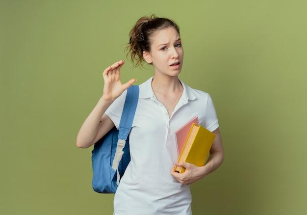 Ontevreden jonge mooie vrouwelijke student die het boek van de achterzakholding en notitieblok draagt die grootte toont die op olijfgroene achtergrond met exemplaarruimte wordt geïsoleerd