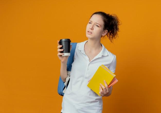 Ontevreden jonge mooie vrouwelijke student die rugtas draagt die boek notitieblok pen en plastic koffiekop houdt die kant bekijkt die op oranje achtergrond met exemplaarruimte wordt geïsoleerd