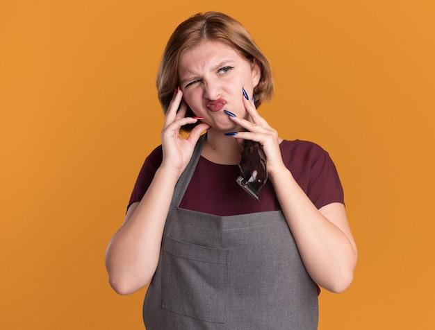 Ontevreden jonge mooie vrouwenkapper die in de trimmer van de schortholding opzij kijkt met verwarringuitdrukking die zich over oranje muur bevindt