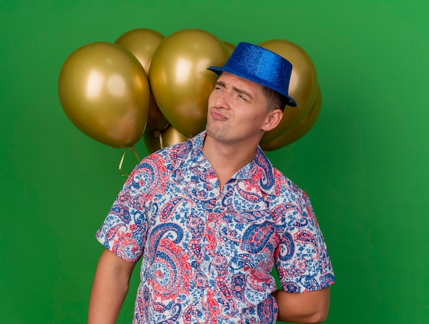 Ontevreden jonge partijkerel die blauwe hoed draagt die zich voor ballons bevindt die op groen worden geïsoleerd